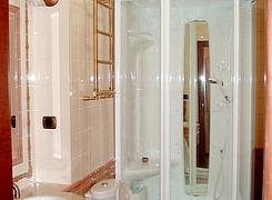 отделка гостевого санузла: укладка плитки и монтаж натяжного бесшовного потолка. На фото также присутствует оригинальная отделка потолочными карнизами